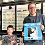 Man and son holding The Smiths and George Michael vinyl records smiling