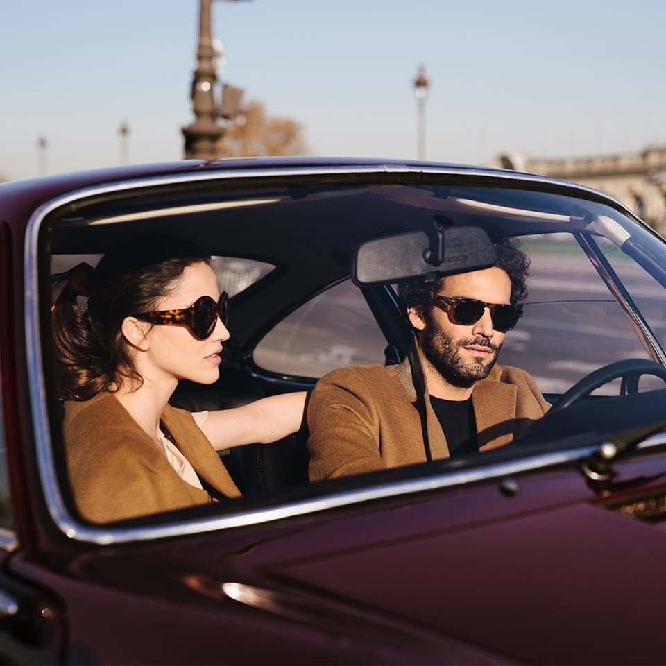 Man driving with woman both wearing sunglasses